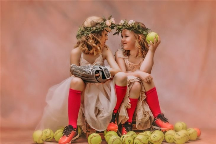 Niñas sentadas sobre una reja mirándose a los ojos, rodeadas de pelotas de tenis, usando vestido estilo princesa y calcetas deportivas, fotografía por Heather Mitchell