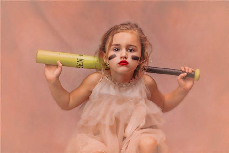 Niña sentada sobre un cajón de madera sosteniendo bat por la espalda, usando vestido estilo princesa fotografía por Heather Mitchell