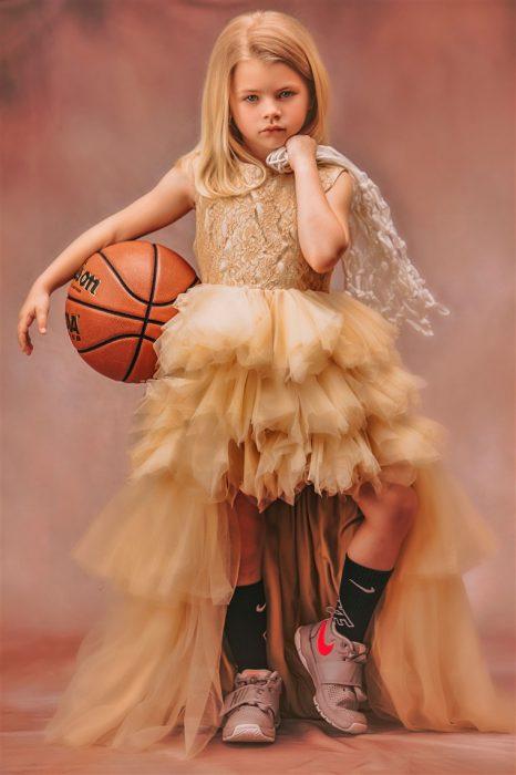 Niña sosteniendo una pelota de basquetball usando vestido de olanes estilo princesa fotografía por Heather Mitchell