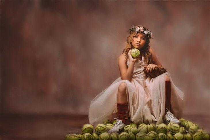 Niña sosteniendo pelotas de tenis sentada en el suelo usando corona de flores y vestido estilo princesa