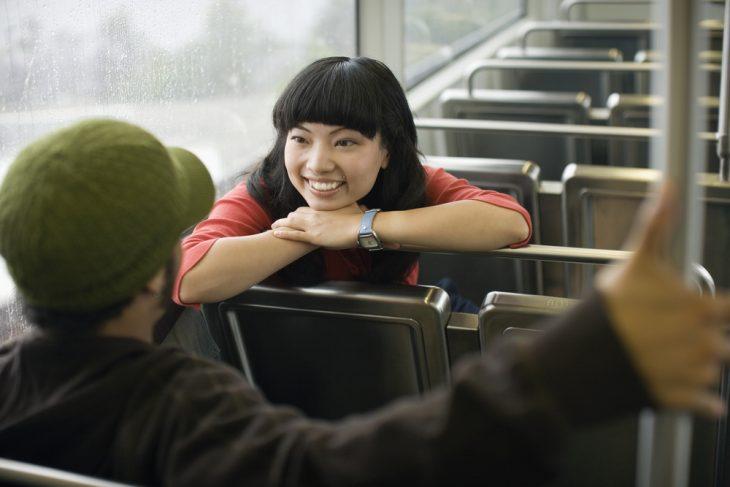 Mujer platicando con un desconocido en el transporte publico