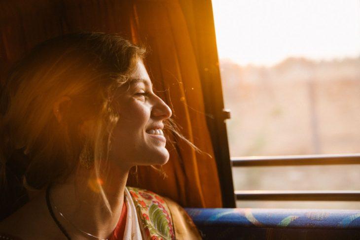 Chica sonriendo felizmente mientras ve el paisaje soleado a través de una ventanilla