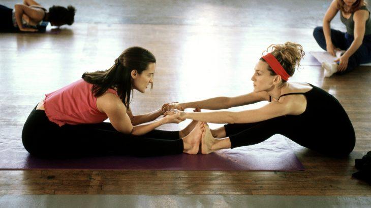 Dos chicas realizando estiramientos en el gimnasio