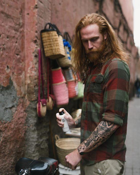 Gwilym C. Pugh, modelo y fotógfrafo, hombre pelirrojo con cabello largo, barba y bigote tupido, con camisa de cuadros y tatuajes en los brazos