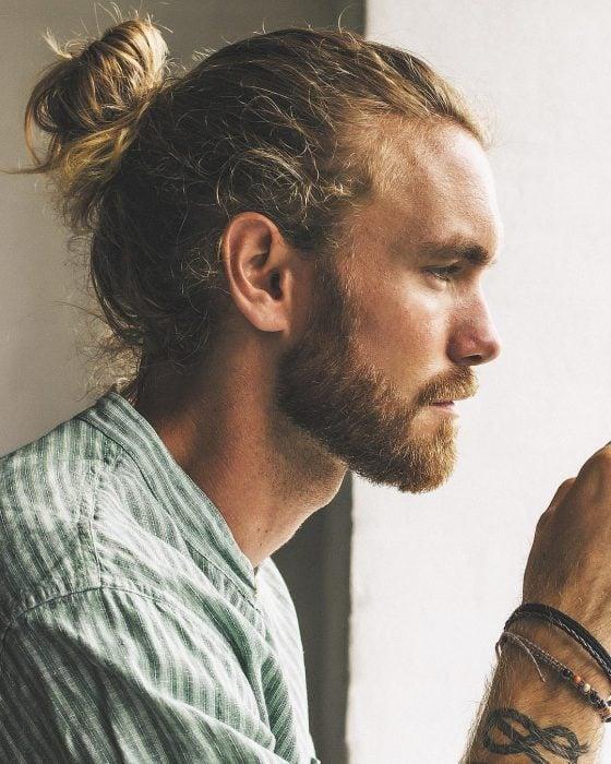 Niels Horvath, hombre de perfil, de cabello rubio con man bun, con barba y bigote corto,