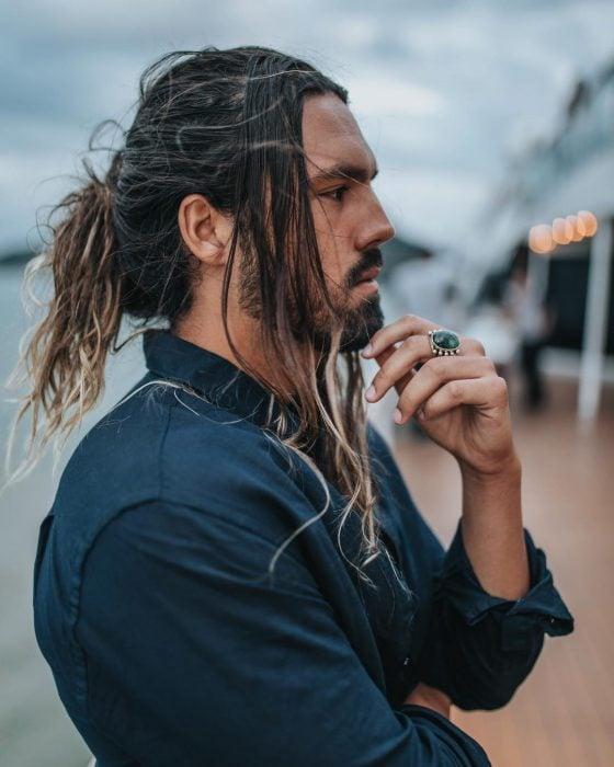 Pedro Giannini, perfil de hombre bronceado con cabello largo teñido, con barba y bigote corto
