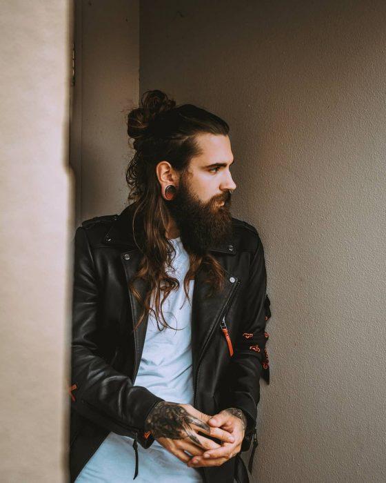 Philip Bottenberg, hombre rockero con cabello castaño largo, recogido con man bun, barba y bigote tupido, con tatuajes en las manos y expansiones en las orejas