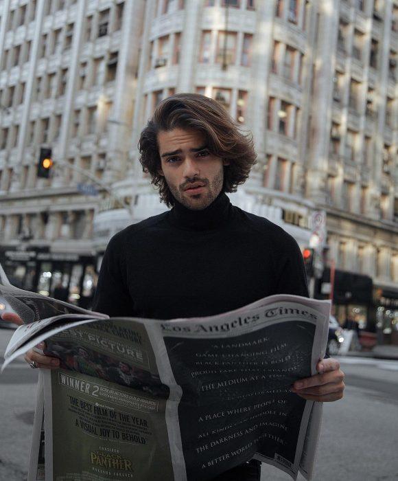 Renan Pacheco, modelo, hombre con el cabello castaño hasta los hombres, con bigote y barba corta, leyendo el periódico en la calle