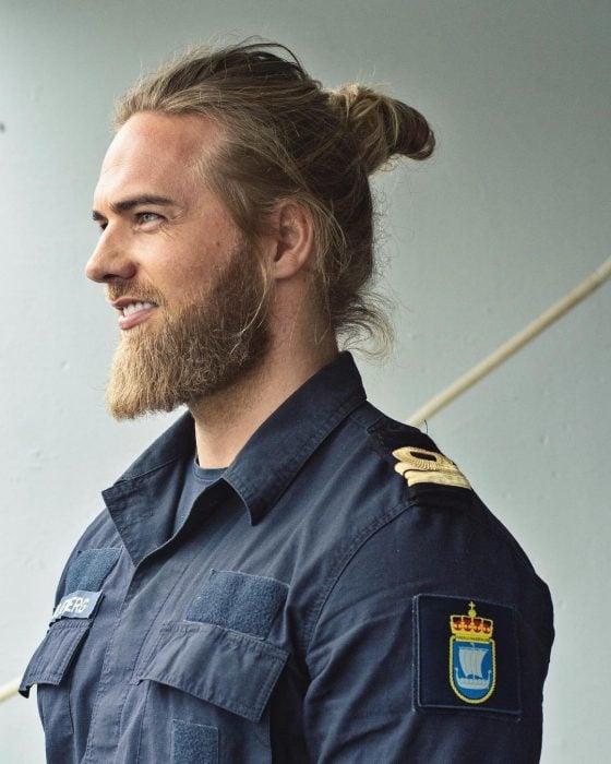 Lasse Lokken Matberg, modelo, hombre uniformado de cabello rubio y largo, con barba y bigote