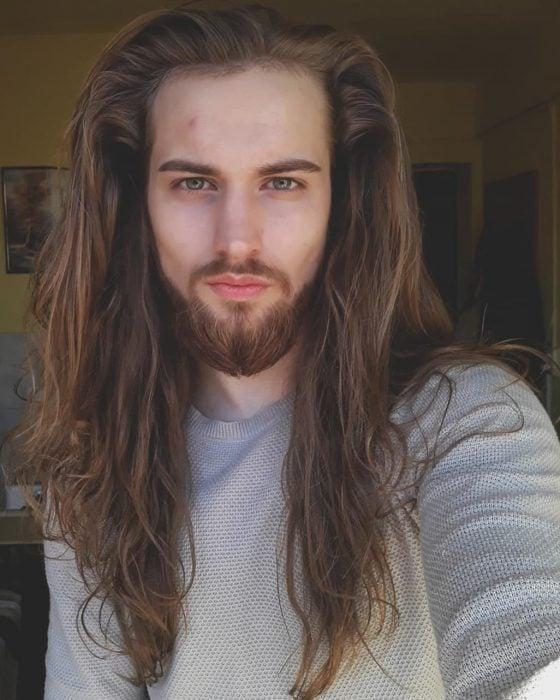 Marcu Daniel, hombre de cabello castaño largo y ondulado, con barba y bigote, ojos verdes