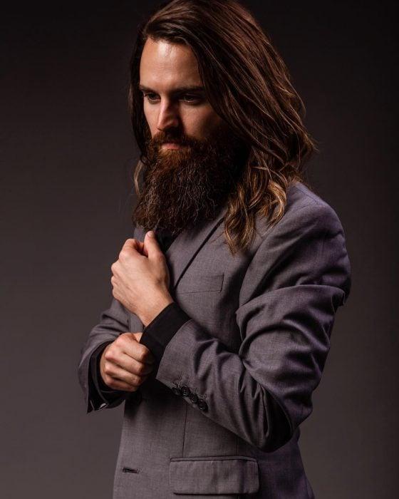 Simon, hombre de cabello largo y castaño, con bigote y barba larga, usando traje gris