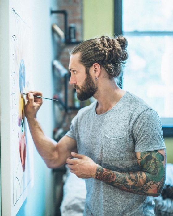 William Tyler, hombre de cabello rubio, largo y peinado man bun, con tatuajes en los brazos pintando un mural en la pared