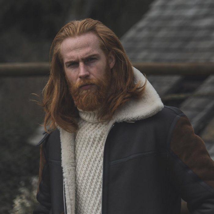Gwilym Pugh, hombre de cabello pelirrojo y largo, con barba y bigote tupidos con cara de enojado