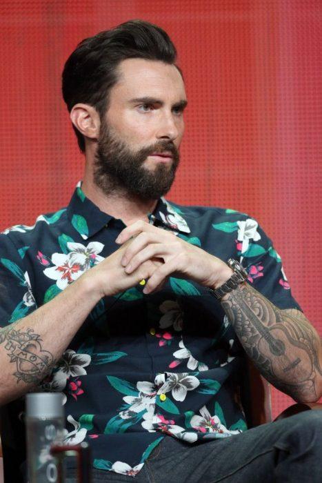 Vocalista de Maroon 5, Adam Levine, hombre sentado, con cabello corto y barba y bigotes, brazos tatuados usando una playera con flores blancas