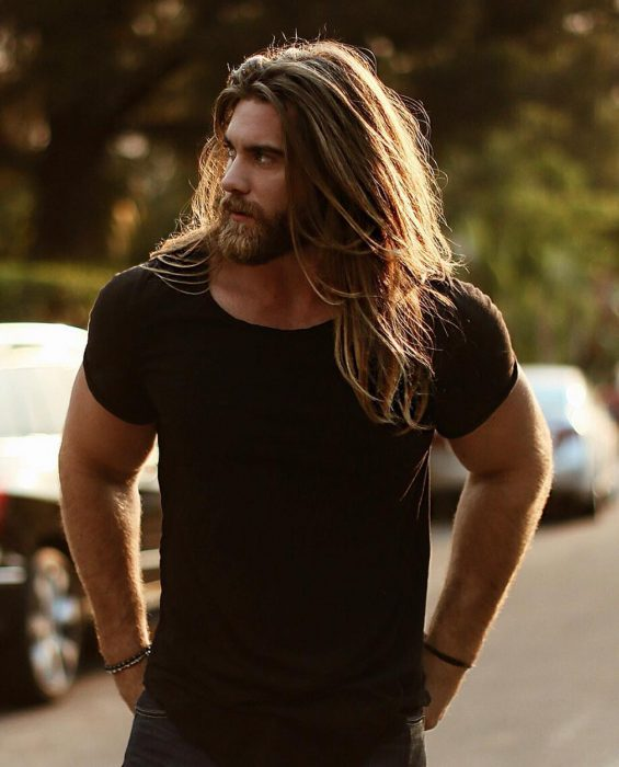 Modelo Brock O'Hurn, hombre musculoso con camisa negra, de cabello largo y castaño, con barba y bigote tupidos