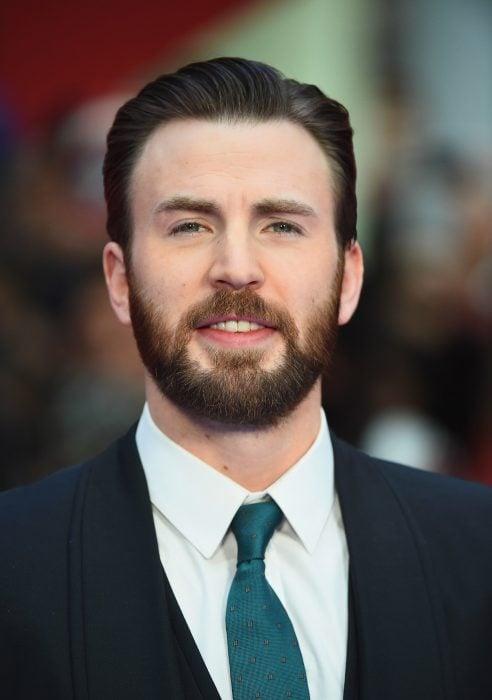 Actor Chris Evans, hombre con cabello corto y peinado para atrás, con barba y bigote poblado, ojos verdes, con traje de gala y corbata verde aqua