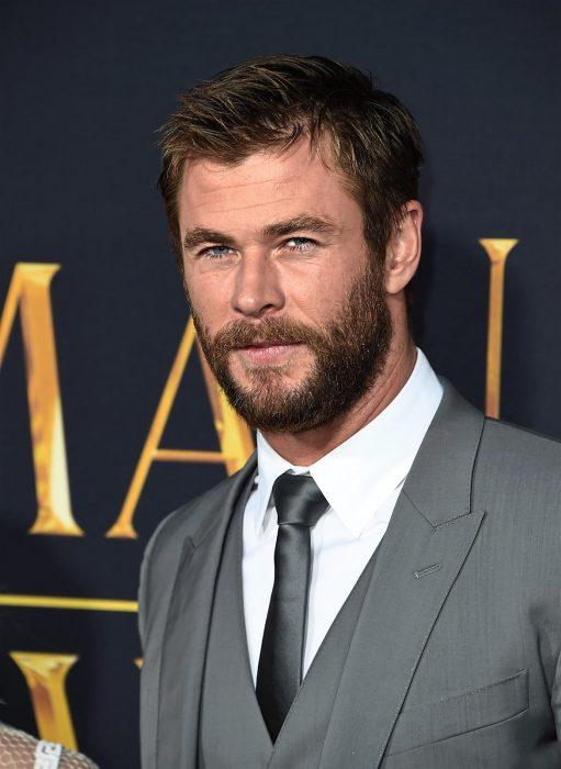 Actor Chris Hemsworth, hombre de cabello corto y rubio, con barba y bigotes tupidos, ojos azules, vestido con traje de gala gris