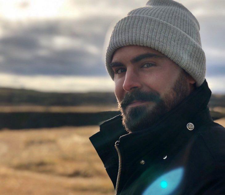 Actor Zac Efron, hombre con barba y bigote tupido, cejas pobladas, con gorro gris para el frío y chamarra