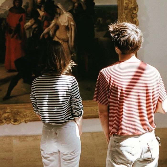 Una pareja de jóvenes disfrutando de una obra de arte en un museo