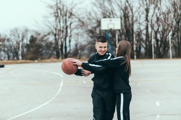 Joven pareja jugando baloncesto en el parque