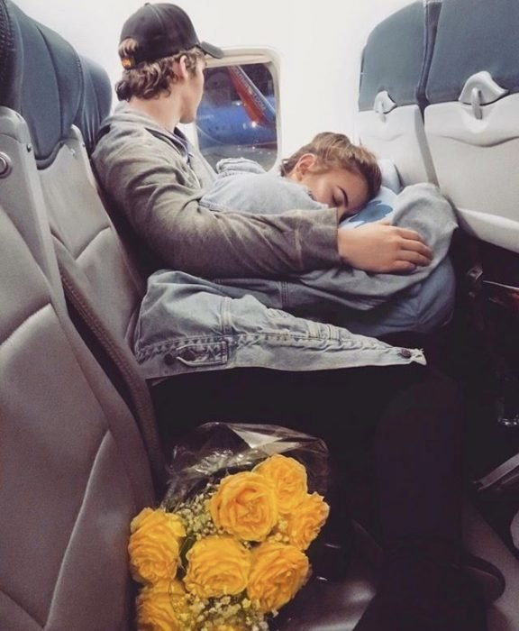 Un joven abrazando a una chica en su regazo mientras viajan en avión