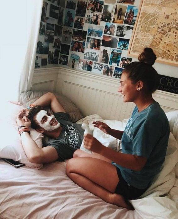 Joven acostado en cama mientras su novia le pone una mascarilla en el rostro
