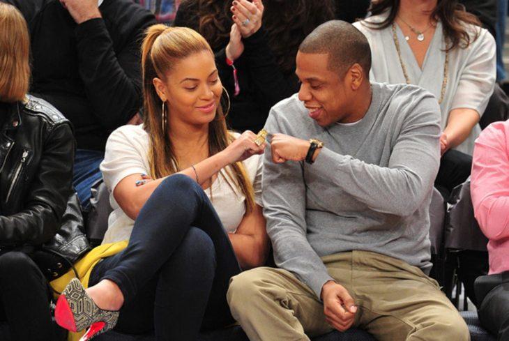 La cantante Beyoncé con el rapero Jay Z en un partido de baloncesto