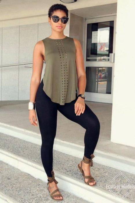 Chica modelando una blusa verde olivo sin mangas holgada y un leggin negro