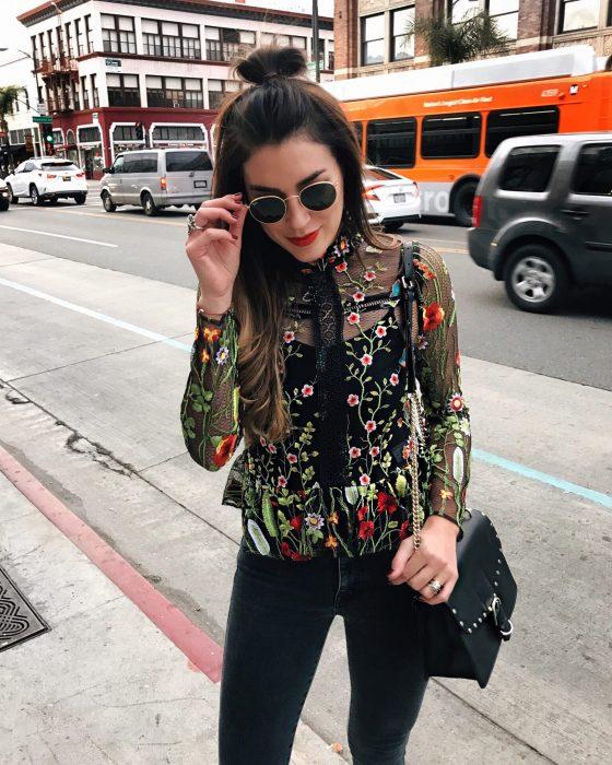 Chica modelando una blusa transparente con detalles en flores y pantalón negro