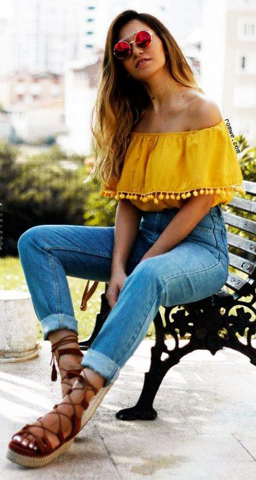 Chica modelando unos jeans de mezclilla y una blusa de hombros descubiertos en color amarillo