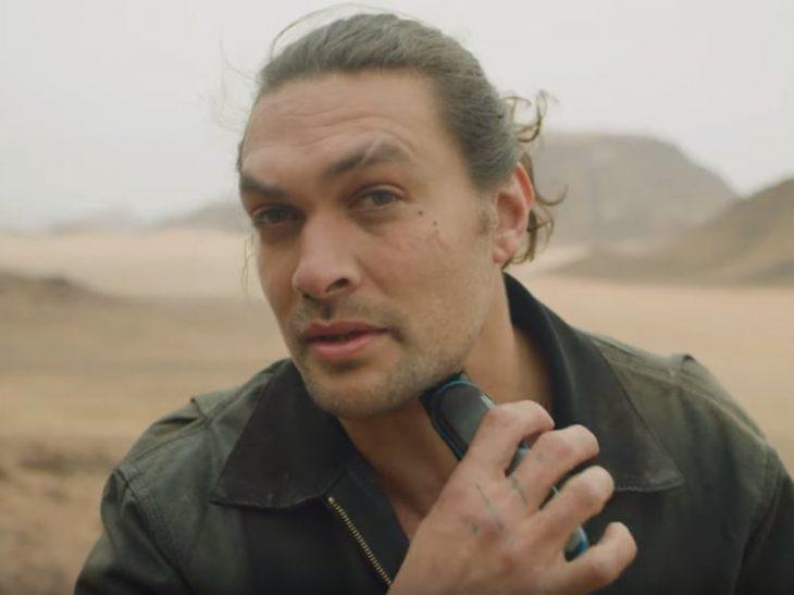 Jason Momoa a mitad de un bosque desertico, afeitando su barba, mientras ve a la cámara