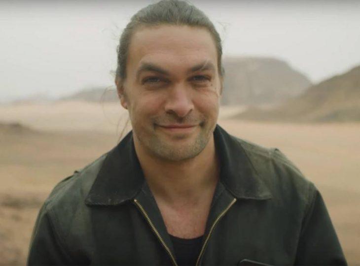 Jason Momoa llevando chaqueta de cuero, sonriendo a la cámara para una fotografía después de afeitar su barba
