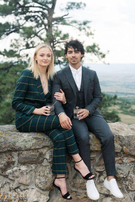 Joe jonas y Sophie turner sentados en una barda con una bebida en la mano