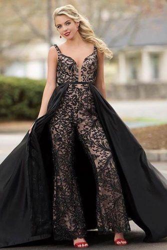 Chica posando para una foto mientras modela un jumpsuit de color negro con encaje y una capa de tul negro