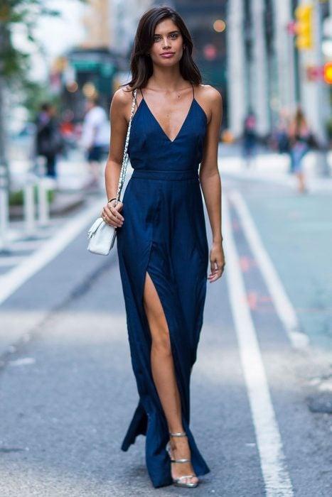 Chica usando un jumpsuit de color azul, bolso y zapatos plateados mientras camina por las calles de Nueva York