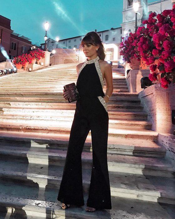 Chica posando para una foto al final de unas escaleras mientras usa un jumpsuit de color negro con aplicaciones de pedrería
