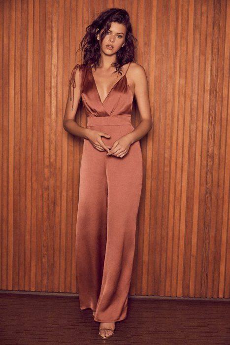 Chica usando un jumpsuit de color rosa gold mientras posa para una foto
