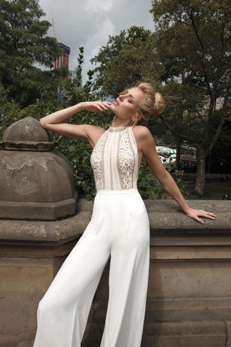 Chica luciendo un jumpsuit blanco con escote de encaje