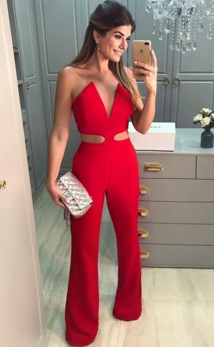 Chica con jumsuit de color rojo, tomándose una fotografía con su celular
