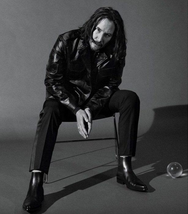 Keanu Revees sentado en una silla con las manos unidas, la cabeza inclinada, cubriendo su rostro con cabello largo, GQ, Jhon Wick: Parabellum