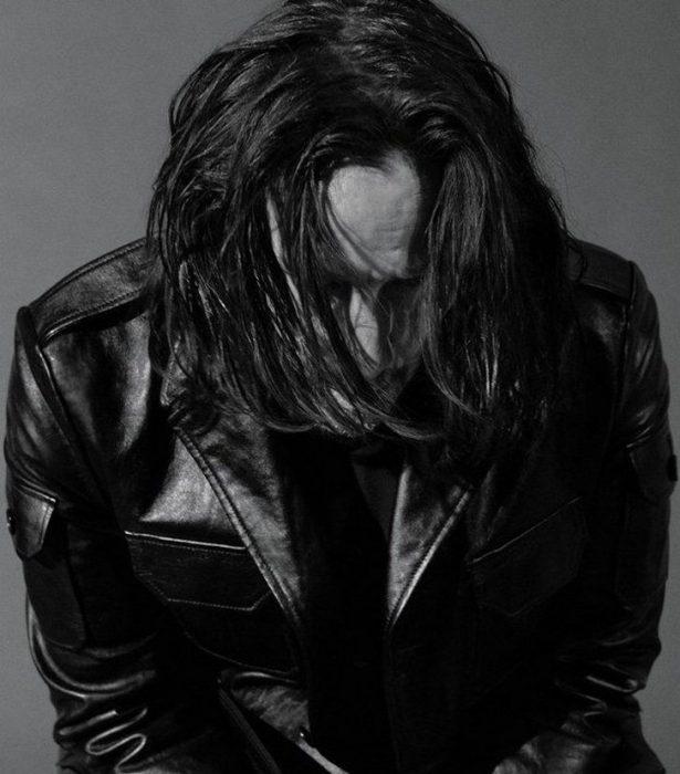 Keanu Reeves con chaqueta de cuero, mirando hacia abajo, cubriendo su rostro con su cabello largo, sentado en una silla, GQ, Jhon Wick: Parabellum