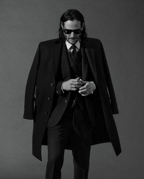 Keanu Revees usando traje sastre en color negro, con las manos unidas, modelando un abrigo, GQ, Jhon Wick: Parabellum