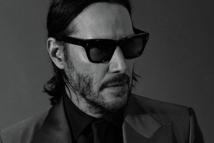 Keanu Reeves con cabello largo peinado hacia atrás con gafas oscuras posando de perfil, GQ, Jhon Wick: Parabellum