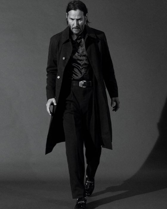 Keanu Revees camiandno dentro de una habitación gris, usando traje sastre, GQ, Jhon Wick: Parabellum