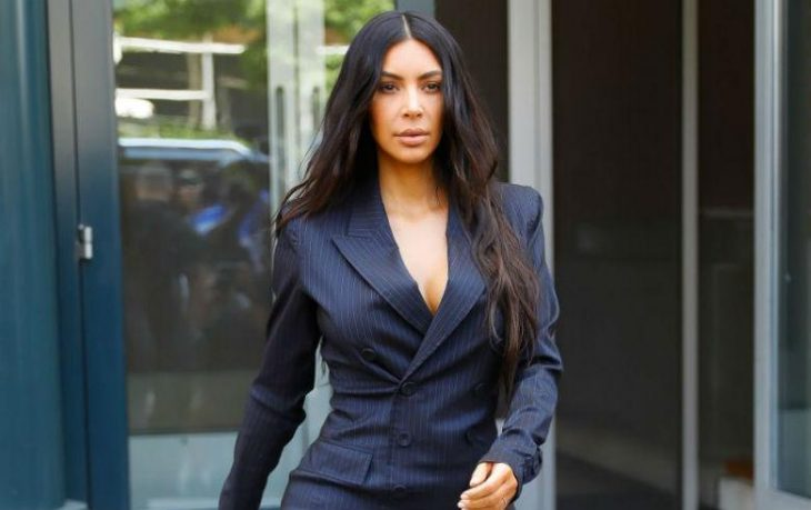 Chica con cabello XXL usando traje sastre negro mientras camina por la calle, Kim Kardashian quiere ser abogada