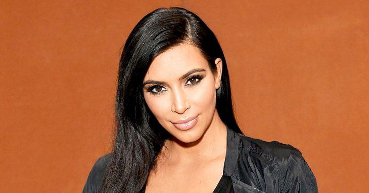 Chica usando ropa oscura, modelando frente a una pred de color naranja, Kim Kardashian, quiere ser abogada