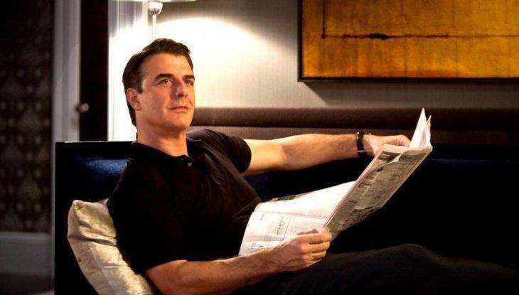 Hombre recostado en una cama mientras lee el periódico
