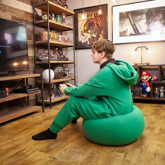Hombre llevando mameluco verde con asiento puff integrado sentadas sobre su propia ropa mientras juega videojuegos
