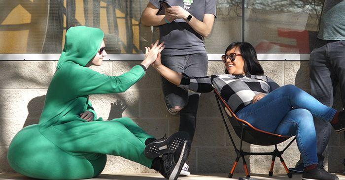 Hombre llevando mameluco verde con asiento puff integrado sentadas sobre su propia ropa mientras saluda a su amigo quien está sentado en una silla de metal durante una fiesta