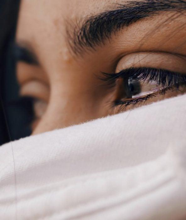 Rostro de una mujer cubierto con una seda blanca que solo deja ver sus ojos llorosos